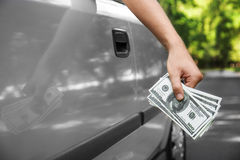 Close up de uma mão que guarda o dinheiro Um homem com os dólares que conduzem um carro em um fundo borrado Esfera 3d diferente C Fotos de Stock Royalty Free