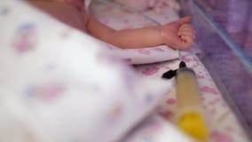 Close-up de uma mão recém-nascida em uma caixa especial para bebês prematuros, ao lado de uma seringa unidade de cuidados intensi video estoque