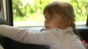 Close-up de uma menina bonito que senta-se no banco de carro vídeos de arquivo