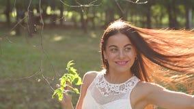 Close-up de uma menina feliz nova que anda em um parque do verão no por do sol Movimento lento vídeos de arquivo