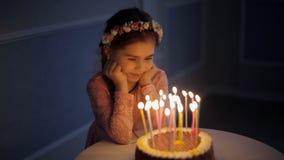 Close up de uma moça perto de um bolo de aniversário com velas filme