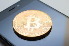 Close-up de uma moeda dourada do bitcoin e de um telefone esperto Imagens de Stock