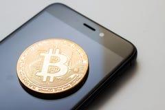 Close-up de uma moeda dourada do bitcoin e de um telefone esperto Fotografia de Stock