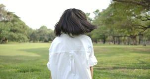 Close-up de uma mulher asiática atrativa nova que anda em um parque do verão no por do sol, vai e gerencie de volta aos olhares n filme