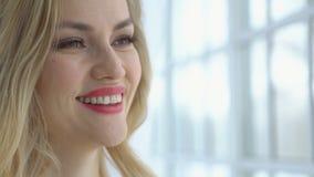 Close-up de uma mulher bonita nova com vidros na janela video estoque