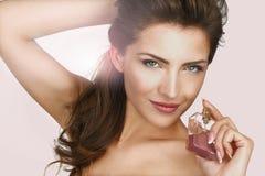 Close up de uma mulher bonita que aplica o perfume imagens de stock