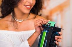 Close up de uma mulher bonita que fixa uma fotocopiadora e que sorri durante reparos da manutenção usando ferramenta handheld Fotografia de Stock Royalty Free