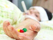 Close up de uma mulher doente nova que encontra-se na cama Foto de Stock