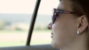 Close-up de uma mulher nos óculos de sol que sentam-se em um carro perto da janela video estoque