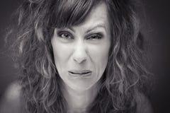 Close-up de uma mulher nova com careta ácida imagens de stock
