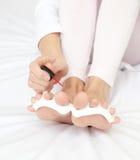 Close-up de uma mulher que faz seu pedicure em uma cama Imagens de Stock