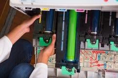 Close up de uma mulher que fixa uma fotocopiadora durante a manutenção, guardando um tonalizador Imagem de Stock Royalty Free