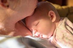 Close up de uma mulher que guarda um bebê recém-nascido de sono no amanhecer adiantado imagem de stock