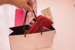 Close up de uma mulher que guarda um saco dos acessórios para comprar cartões, carteira, telefone Vendas do conceito, sexta-feira Fotos de Stock Royalty Free