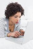 Close up de uma mulher séria que usa o portátil na cama Fotos de Stock Royalty Free