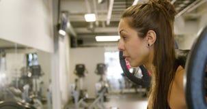 Close-up de uma ocupa desportiva do treinamento da mulher com pesos pesados no gym da aptidão vídeos de arquivo