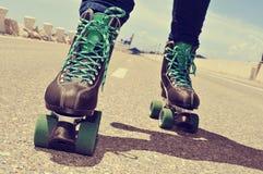 Close up de uma patinagem de rolo do homem novo, com um ef cruz-processado Imagens de Stock