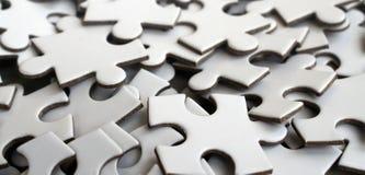 Close-up de uma pilha de elementos uncompleted de um enigma branco Um grande número de partes retangulares de um grande mosaico b imagens de stock