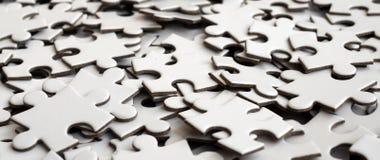 Close-up de uma pilha de elementos uncompleted de um enigma branco Um grande número de partes retangulares de um grande mosaico b imagem de stock