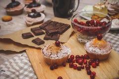 Close-up de uma placa clara de desbastamento em um guardanapo de linho de linho, em que bagas vermelhas, queques, chocolate fotos de stock