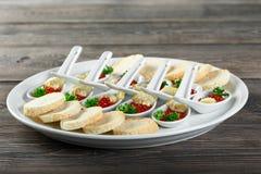 Close-up de uma placa grande com os petiscos feitos do pão, dos limões e do caviar imagem de stock royalty free
