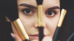 Close-up de uma posição bonita nova da menina em um fundo preto Durante isto, guarda quatro escovas para a composição filme