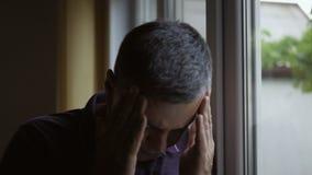 Close-up de uma posição do homem na janela, guardando suas mãos sobre sua cabeça que sofre de uma dor de cabeça video estoque