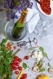 Close up de uma tabela cinzenta com placa, champanhe, tomates, aspargo, vidros, corkscrew, feijões em um fundo cinzento Fotos de Stock Royalty Free