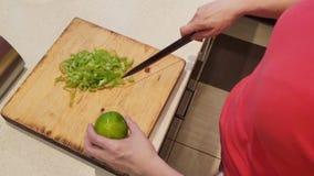 Close-up de vrouw snijdt thuis groene paprika op houten raadskeuken stock video