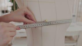 close-up De vrouwelijke kledingsontwerper werkt met metingenledenpoppen in de naaiende studio Zij meet langs stock video