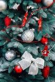 Close up decorado da árvore de Natal Bolas vermelhas e douradas e festão iluminada com lanternas elétricas Macro das quinquilhari fotografia de stock royalty free
