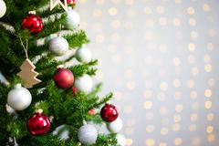 Close up of decorated christmas tree over white brick wall with Stock Image