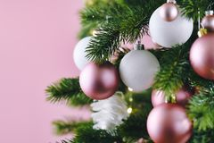Close up of decorated Christmas tree with white seasonal and pink tree ornaments like baubles and stars on pink background