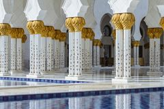 Close-up decorated marble columns on the top with like golden palm with reflected pool in front of Sheikh Zayed Grand Mosque Stock Image