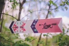 Close-up decorative arrow-pointer with inscription «love» hanging on branch tree on nature royalty free stock photo