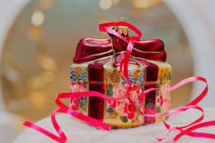 Close up of decorative Christmas decoration at a gift box with red ribbons on gold blurred background. Selective focus Royalty Free Stock Images