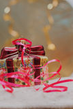 Close up of decorative Christmas decoration at a gift box with red ribbons on gold blurred background. Selective focus Stock Photography