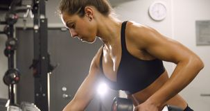 Close-up of dedicated woman training and lifting weights in fitness gym. Close-up of weights training woman in fitness gym lifting weights and showing strong stock video
