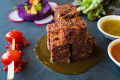 Close up  deep fried crispy pork knuckle cube with spicy sauce and tomato ,  fusion style Royalty Free Stock Photo