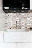 Close up of a deep white kitchen sink and tiled splashback Stock Images