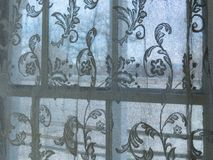 Close up of delicate lace curtain hanging in window stock image