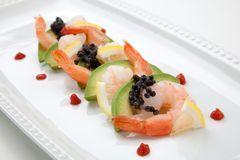 Shrimp Cocktail with Black Caviar. Close up of delicious appetizer shrimp cocktail with black caviar. Garnished with avocado, lemon, and horseradish cocktail Royalty Free Stock Photo