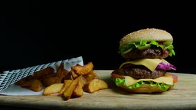 Close up of delicious burger with double cheese and french fries. Black background. Close up of delicious burger with double cheese and french fries on the stock video