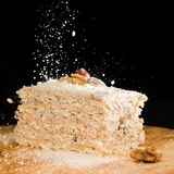 Close-up delicious cake of puff pastry with sour cream and walnut sprinkled crumbs on a wooden plate on dark background royalty free stock photos