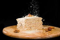 Close-up delicious cake of puff pastry with sour cream and walnut sprinkled crumbs on a wooden plate on dark background royalty free stock images