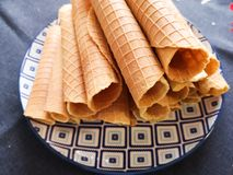 Close-up of delicious chocolate waffle rolls lie on white plate. Preparation of a sweet dessert. White clean kitchen and table. Many wafer tubules are group stock images