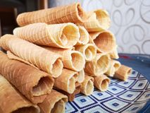 Close-up of delicious chocolate waffle rolls lie on white plate. Preparation of a sweet dessert. White clean kitchen and royalty free stock photo