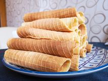 Close-up of delicious chocolate waffle rolls lie on white plate. Preparation of a sweet dessert. White clean kitchen and table. Many wafer tubules are group royalty free stock photos