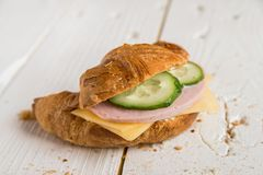 Croissant with ham, cheese and cucumber stock image