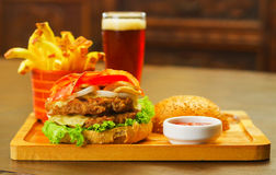 Close up of a delicious hamburger with beef, bacon, onion, tomato, lettuce and cheese with the upper piece of bread with. A glass of beer and french fries Royalty Free Stock Photography